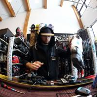 An worker adjusts skis and boots at a rental shop at the Niseko Hanazono resort in Hokkaido. | BLOOMBERG