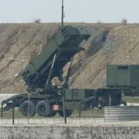 Self-Defense Forces members work around a PAC-3 Patriot missile unit deployed on Ishigaki Island, Okinawa Prefecture, in February. | KYODO