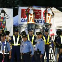 Police stand guard in the Kasumigaseki district as Tokyo District Court officials remove tents set up years ago by anti-nuclear activists angered by the Fukushima disaster, at 3:59 a.m. Sunday. | KYODO
