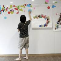 An employee decorates a wall at a nursery school, operated by Doronkokai, in Tokyo.   BLOOMBERG