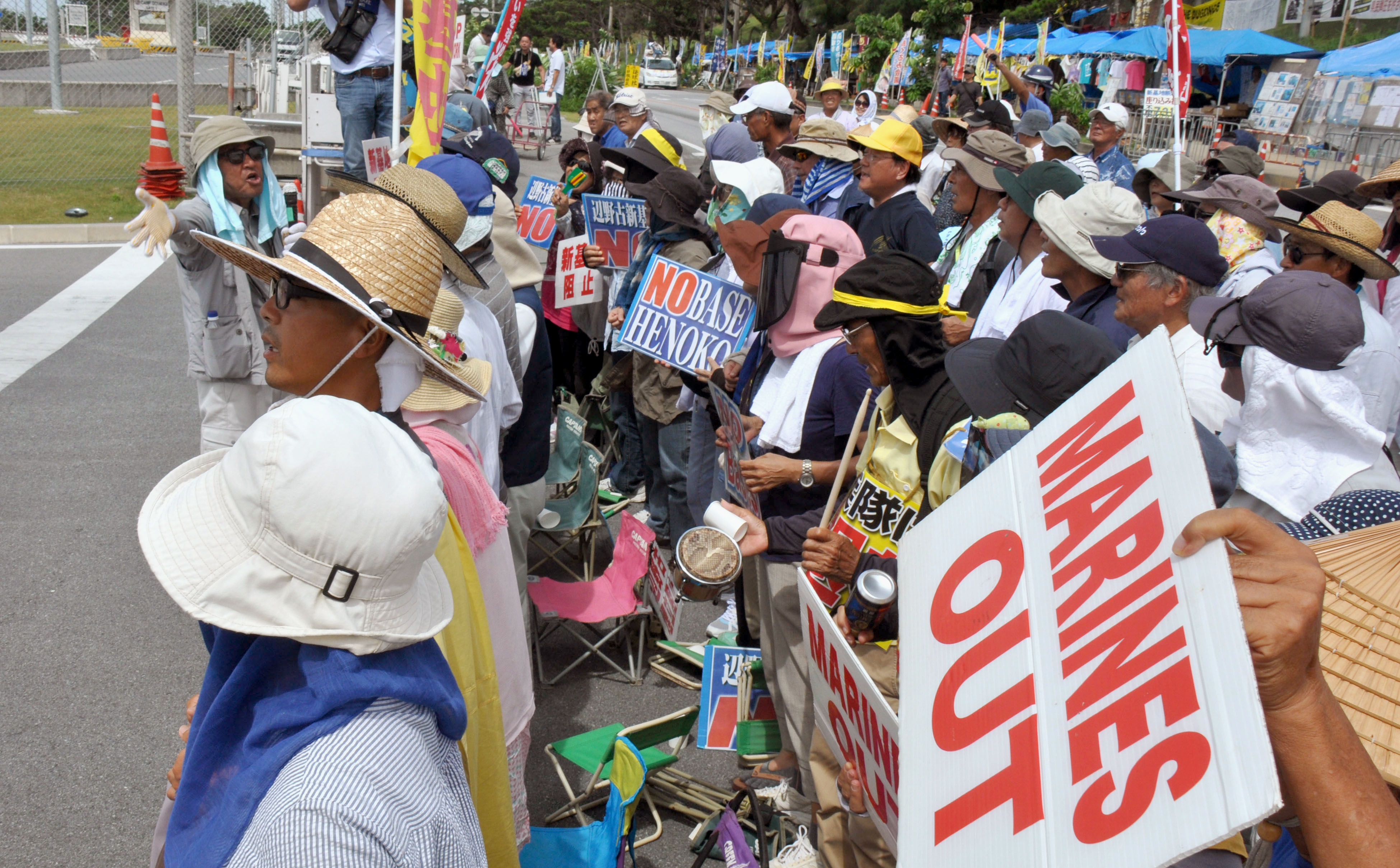 Citizens who oppose construction of the Futenma replacement base in Okinawa Prefecture protest at the gate of Camp Schwab on July 6. | KYODO