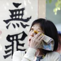 Keiko Aoki expresses relief Wednesday outside the Osaka District Court, which said the confessions were invalid.   KYODO