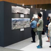 Visitors take in a Japanese photojournalism exhibition at the Tokyo International Forum on Saturday. The display of momentous news events ends on Sept. 9. | KYODO