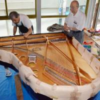 Teruo Inoue (right) oversees repairs to a grand piano damaged by the March 2011 tsunami that will be donated to a hospital in Ishinomaki, Miyagi Prefecture, at his shop in the city last month. | KYODO