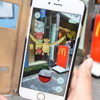 A woman plays Nintendo's 'Pokemon Go' game on her smartphone in front of a McDonald's restaurant in Tokyo's Akihabara shopping district. | AFP-JIJI