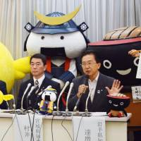 Iwate Gov. Takuya Tasso (raising hand) addresses a news conference in Tokyo on Wednesday as Miyagi Gov. Yoshihiro Murai and other municipal officials look on. | KYODO