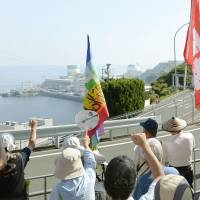 Protesters rally Friday on a hill overlooking the Ikata nuclear power plant in Ehime Prefecture, which was restarted the same day. | KYODO