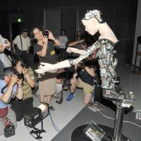 Journalists gather around Alter to take photos of the robot at the National Museum of Emerging Science and Innovation (Miraikan) in Tokyo on July 29. | YOSHIAKI MIURA