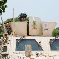 A member of the Self-Defense Forces keeps watch from atop an armored vehicle during U.N. peacekeeping operations in Juba on March 8. The new security law gives the SDF greater scope to use arms while participating in peacekeeping. | KYODO