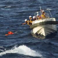 Japan Coast Guard personnel pull Chinese crew from the ocean after their fishing boat collided with a cargo ship and sank near the Senkaku Islands early Thursday.   JAPAN COAST GUARD / VIA KYODO