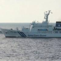 A screen shot from Japan Coast Guard video footage shows one of its patrol ships (right) warning a Chinese government ship to leave Japanese territorial waters near the Senkakus. | JAPAN COAST GUARD / VIA KYODO