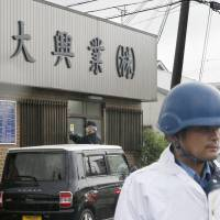 A police officer stands guard Monday in front of the office of Wadai Kogyo, a construction company in the city of Wakayama. | KYODO