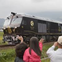 Local residents wave at the Seven Stars luxury sleeper train as it runs through Yufu, Oita Prefecture, in October 2013.   KYODO