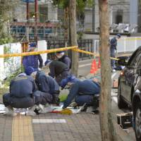 Police officers check the scene Tuesday in the city of Chiba, where a 14-year-old girl was stabbed earlier on the day. | KYODO