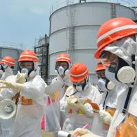 Journalists in hazmat suits are briefed on the work process at the Fukushima No. 1 nuclear power plant in the town of Okuma, Fukushima Prefecture, in June 2014. | KYODO