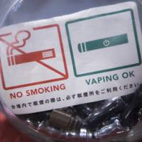 A 'No Smoking' 'Vaping OK' sign sits on display at the Vaping Ape store in Tokyo on Aug. 23, 2016. | BLOOMBERG