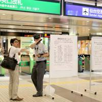 A Sendai Station employee guides a customer, as many train lines in Sendai, Miyagi Prefecture, were affected by Typhoon Chanthu, which moved north off Japan's Pacific coast Wednesday. | KYODO