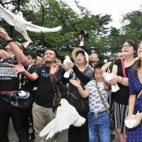 Visitors to Yasukuni Shrine in Tokyo release doves in a gesture of peace Monday as Japan marked the 71st anniversary of its surrender in World War II. | YOSHIAKI MIURA