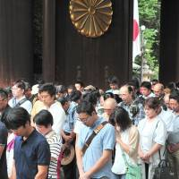 Visitors to Yasukuni Shrine in Tokyo observe a moment of silence at noon on Monday, the 71st anniversary of Japan's defeat in World War II. | YOSHIAKI MIURA