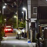 Police investigators are seen near site where Yasuhide Mizobata, the suspect of a Monday fatal shooting in the city of Wakayama, was found early Wednesday morning. | KYODO