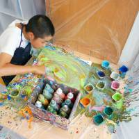 Kentaro Hayashi, a 13-year-old student with learning disabilities, gets down and dirty with colorful paints at atelier incurve jr. in Osaka on June 22. | KYODO