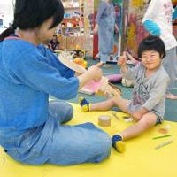 An elementary school student with learning disabilities works on an art piece at after-school day care service Borderless Art Space HAP in Hiroshima on May 21. | KYODO