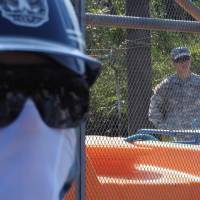 Heavy presence: As private security guards stand outside, a U.S. soldier watches through the fence from inside the site where new helipads are being built within the U.S. Marine Corps Northern Training Area in northern Okinawa. | JON MITCHELL