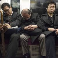 Commuters sleep on a train in Tokyo. | ROB GILHOOLY