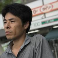 Fumiyoshi Shimizu stands outside the convenience store at which he currently works in Tokyo on Aug. 1. | ROB GILHOOLY