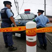 Senseless: Police officers stand guard in front of a facility for people with disabilities in Sagamihara, Kanagawa Prefecture, last month after a knife attack that left 19 of its residents dead. | REUTERS