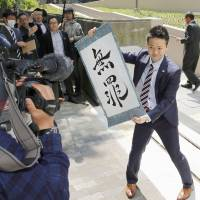 Winning: Motonobu Ishigaki holds up a ruling handed down by the Osaka District Court in 2014 that acquitted Osaka Club Noon of violating laws that uphold public morals.