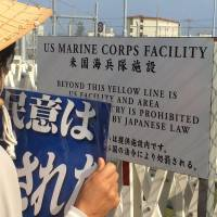 Trans-Atlantic partnership: Demonstrators block the gates of Camp Schwab, site of the proposed relocation of U.S. Marine Corps Air Station Futenma. The British Ministry of Defence has revealed that two Royal Marine officers have been deployed to Schwab in Nago and Camp Hansen in central Okinawa. | JON MITCHELL