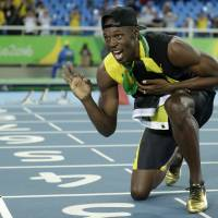 Bolt celebrates by throwing javelin