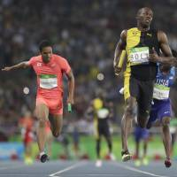 Usain Bolt crosses the finish line to win the 4x100-meter relay for Jamaica on Friday night and claim his third gold medal of the Rio Olympics and ninth of his Olympic career. Japan's Aska Cambridge (left) led his team to a historic silver medal. | AP