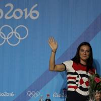 Russian pole vaulter Yelena Isinbayeva waves as she leaves a press conference to announce her retirement in Rio de Janeiro on Friday. | AP