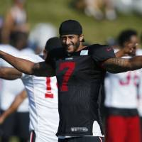 Niners' Kaepernick protests by sitting during U.S. anthem