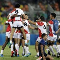 Japan's players celebrate after winning the men's rugby sevens match against France at the Summer Olympics in Rio de Janeiro Wednesday. | AP