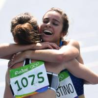 New Zealand's Nikki Hamblin (left) hugs Abbey D'Agostino of the United States after they competed in the the first round of the women's 5,000-meter competition at the Rio Olympics on Tuesday in Rio de Janeiro. | AFP-JIJI