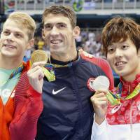 Silver medalist Masato Sakai (right) poses with winner Michael Phelps (center) and Tamas Kenderesi, the bronze medalist, after the men's 200-meter butterfly final on Tuesday in Rio de Janeiro. | KYODO