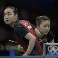 Japan's Mima Ito (left) serves as doubles partner Ai Fukuhara stands ready during their bronze-medal match against Singapore at the Rio Olympics on Tuesday. | AFP-JIJI