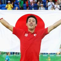 Kei Nishikori holds up a Japanese flag after beating Rafael Nadal to win the bronze medal in the men's tennis singles at the Rio Olympics on Sunday. | KYODO