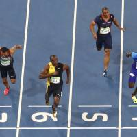 Usain Bolt crosses the finish line first to win the 100-meter final at the Rio Olympics on Sunday night. Bolt won his third straight Olympic gold in a time of 9.81 seconds. | REUTERS