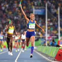 U.S. runner Allyson Felix begins to celebrate as she crosses the finish line to give the Americans the victory in the women's 4x400 relay at the 2016 Summer Games on Saturday in Rio de Janeiro. | AFP-JIJI