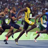 Jamaica's Usain Bolt (center) runs in the 100-meter final at the 2016 Summer Olympics on Sunday in Rio de Janeiro. | AFP-JIJI