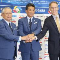 NPB commissioner Katsuhiko Kumazaki (left), Samurai Japan manager Hiroki Kokubo and MLB Vice President for Asia Jim Small pose for a photo at a news conference in Tokyo on Tuesday for the 2017 World Baseball Classic. | KAZ NAGATSUKA