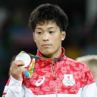 Shinobu Ota stands on the podium after taking the silver medal in the 59-kg Greco-Roman wrestling event on Sunday. | AFP-JIJI