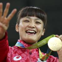 Kaori Icho celebrates winning her fourth straight Olympic gold medal after beating Russia's Koblova Zholobova in the women's 58-kg final at the Rio Games on Wednesday. | REUTERS