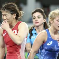 Saori Yoshida (left) reacts after losing to Helen Maroulis of the United States in the women's 53-kg freestyle final at the Rio Olympics on Thursday. | REUTERS