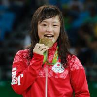 Japan's Eri Tosaka celebrates on the podium after winning in the women's 48-kg freestyle wrestling event at the Carioca Arena 2 in Rio de Janeiro on Wednesday during the Rio 2016 Olympic Games. | AFP-JIJI