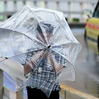 A man's umbrella proves to be no match for the heavy winds of Typhoon Mindulle. | SATOKO KAWASAKI